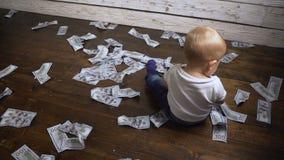 Het kind zit op de vloer met geld stock videobeelden