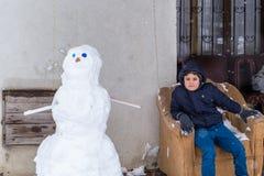 Het kind zit op een laag nadat hij sneeuwman beëindigde Royalty-vrije Stock Foto's