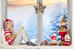 Het kind zit op het venster en schrijft een brief aan Santa Claus Vrolijke Kerstmis en Gelukkige Vakantie! royalty-vrije stock afbeelding