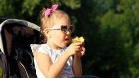 Het kind in zonnebril zit in een wandelwagen en eet een appel bij zonsondergang Het meisjesclose-up van de portretbaby op een zon stock video