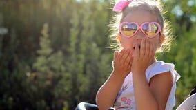 Het kind in zonnebril zit in een wandelwagen en verzendt luchtkussen bij zonsondergang stock videobeelden