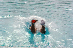 Het kind zwemt en duikt in de pool Stock Fotografie