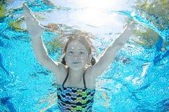Het kind zwemt onderwater in zwembad, duikt het gelukkige actieve tienermeisje en heeft pret onder water, jong geitjefitness en s stock foto