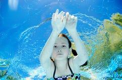 Het kind zwemt onderwater in zwembad, duikt het gelukkige actieve tienermeisje en heeft pret onder water, jong geitjefitness en s stock afbeeldingen