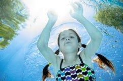 Het kind zwemt onderwater in zwembad, duikt het gelukkige actieve tienermeisje en heeft pret onder water, jong geitjefitness en s royalty-vrije stock fotografie