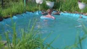 Het kind zwemt op een opblaasbare cirkel in een kleine vijver Tuingebied, bloemen en installaties rond het meer gelukkig stock video