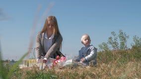 Het kinderenvoedsel, jonge moeder voedt kleine peuterjongen met chocoladesuikergoed tijdens familiepicknick op aard stock videobeelden