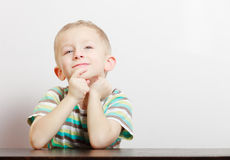 Het kindjong geitje van de portret blond peinzend nadenkend jongen bij de lijst binnen royalty-vrije stock afbeelding