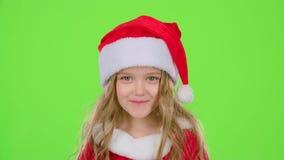 Het kindmeisje in een mooi kostuum en een rood Nieuwjaar ` s GLB glimlacht Het groene scherm stock video