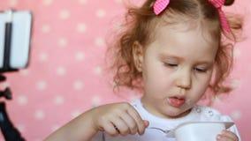 Het kindmeisje eet voedsel en kijkt beeldverhalen op smartphone De gelukkige jonge zakken van de meisjesholding op een witte acht stock video