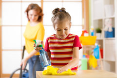 Het kindmeisje en haar moeder maken thuis het schoonmaken in ruimte stock foto's