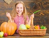 Het kindmeisje geniet het landbouwbedrijf van leven Het organische Tuinieren Jong geitjelandbouwer met oogst houten achtergrond K royalty-vrije stock afbeeldingen
