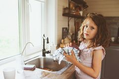 Het kindmeisje helpt schotels in keuken thuis baren en wassen Toevallige levensstijl in echt binnenland royalty-vrije stock foto