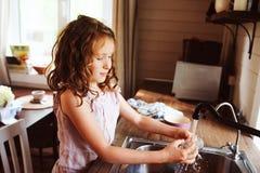 Het kindmeisje helpt schotels in keuken thuis baren en wassen Toevallige levensstijl in echt binnenland stock foto's