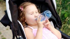 Het kindmeisje ligt in een kinderwagen en drinkt water van een fles Dorst in de zomer stock footage