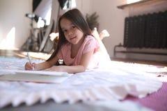Het kindmeisje ligt op de mat en trekt royalty-vrije stock foto's