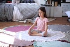 Het kindmeisje maakt yogaoefeningen op de mat stock afbeeldingen