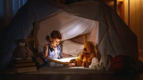 Het kindmeisje met een boek en een flitslicht en een teddybeer vóór gaan royalty-vrije stock afbeeldingen