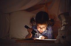 Het kindmeisje met een boek en een flitslicht en een teddybeer vóór gaan stock afbeeldingen
