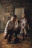 Het kindmeisje met vrouw in beeld van Sherlock Holmes bevindt zich naast Engelse buldog op achtergrond van spiegel en oud binnenl stock foto