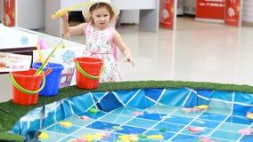 Het kindmeisje op de speelplaats speelt een spel van visserij, vangt de vissen in de pool en stapelt het in een emmer op stock video