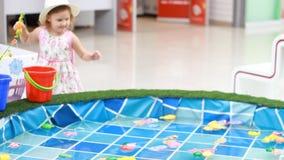 Het kindmeisje op de speelplaats speelt een spel van visserij, vangt de vissen in de pool en stapelt het in een emmer op stock footage