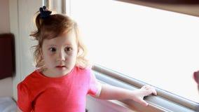 Het kindmeisje reist door trein Babyreizen door spoor en en blikken uit het venster stock videobeelden