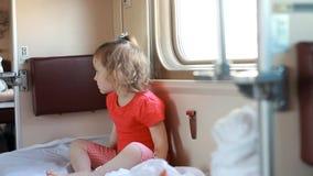 Het kindmeisje reist door trein Babyreizen door spoor en slaap Conceptenrente, nieuwsgierigheid, verwachting stock videobeelden