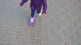 Het kindmeisje rolt op skateboard op de straat stock video