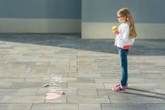 Het kindmeisje schreef op het asfalt Ik houd van mijn planeet Eet een appel en bekijkt de tekst, gezonde levensstijl, het gezonde stock foto