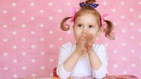 Het kindmeisje slaat haar handen, verheugt zich, applaus Portret van een grappige baby die close-up toejuicht stock videobeelden