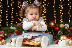 Het kindmeisje verbergt haar speelgoed, portret in Kerstmisdecoratie, het concept van de de wintervakantie, donkere achtergrond m Royalty-vrije Stock Afbeelding