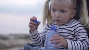 Het kindmeisje zit in een babywandelwagen en drinkt water van een fles stock video