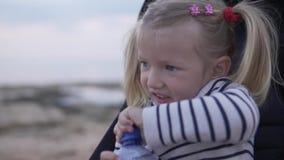 Het kindmeisje zit in een kinderwagen en drinkt water van een fles stock video