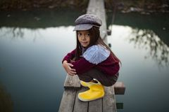 Het kindmeisje zit op houten brug op achtergrond van rivier stock fotografie