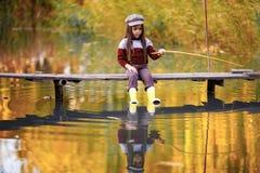 Het kindmeisje zit op houten visserijbrug en vangt vissen in aut stock afbeelding