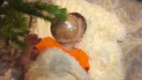 Het kindspel in de ruimte van de kinderen met Kerstboom De jongen ligt op een witte pluizige deken Gelukkige kinderjaren stock footage