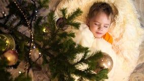 Het kindspel in de ruimte van de kinderen met Kerstboom De jongen ligt op een witte pluizige deken Gelukkige kinderjaren stock video