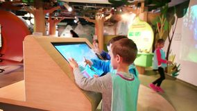 Het kindspel met aanrakingspaneel, spel van de jongens het speelcomputer, Kinderen beweegt hun vingers langs het grote aanrakings stock video