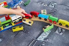 Het kindspel met houten trein, bouwt stuk speelgoed thuis spoorweg of kleuterschool Het spel van het peuterjonge geitje met houte stock afbeeldingen