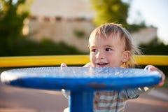 Het kindspelen van de babyjongen op speelplaatsgebied Stock Foto's