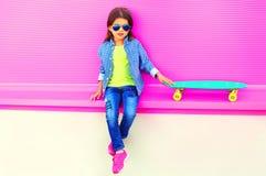 Het kindzitting van het maniermeisje met skateboard in stad op kleurrijke roze muur royalty-vrije stock afbeeldingen