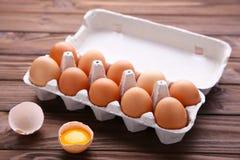 Het kippenei is half gebroken onder andere eieren Kippeneieren in containers op bruine houten achtergrond royalty-vrije stock afbeelding