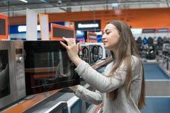 Het klantenmeisje kiest een magnetron in een opslag van het huistoestel stock foto