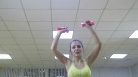 Het klassieke bodybuilding De spiervrouw die van de blondegeschiktheid oefeningen in de gymnastiek doen Geschiktheid - concept ge stock video