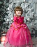 Het kleine aanbiddelijke vrouwelijke kind in roze kleding houdt sneeuw in zijn handen, Nieuwjaar` s decoratie Royalty-vrije Stock Afbeelding