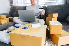 Het kleine bedrijfspakket voor verzending aan cliënt, Jonge mens ontving online het winkelen pakket het openen dozen en het kopen royalty-vrije stock fotografie