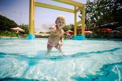 het kleine blondemeisje zwemt met vreugde in water van pool Royalty-vrije Stock Foto