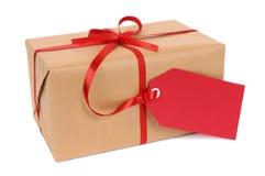 Het kleine de pakpapierpakket of gift bond met rood die lint en giftmarkeringsetiket op witte achtergrond wordt geïsoleerd Stock Foto