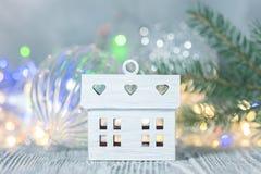 Het kleine decoratieve huis tegen vage het gloeien vakantie steekt achtergrond met sparrentak aan royalty-vrije stock afbeelding